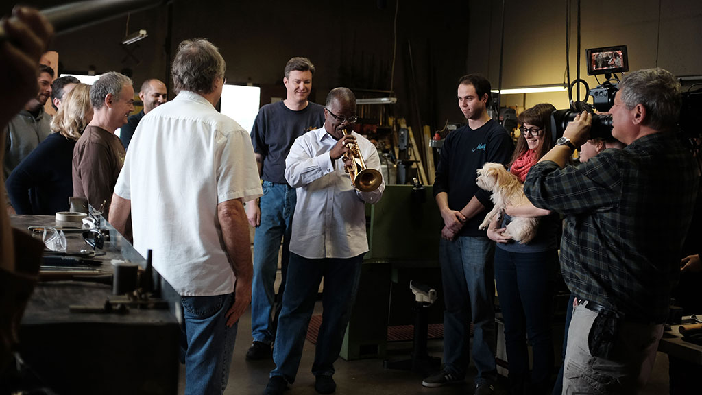 Monette employees and Craft in America crew listen as Scotty Barnhart tests the latest trumpet