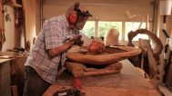 David Holzapfel uses a chainsaw to carve a burl
