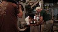 Glass shop founder Hugh Jenkins assists a student