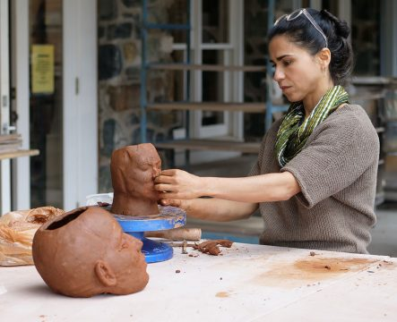 Cristina Cordova sculpting a head in clay, Identity