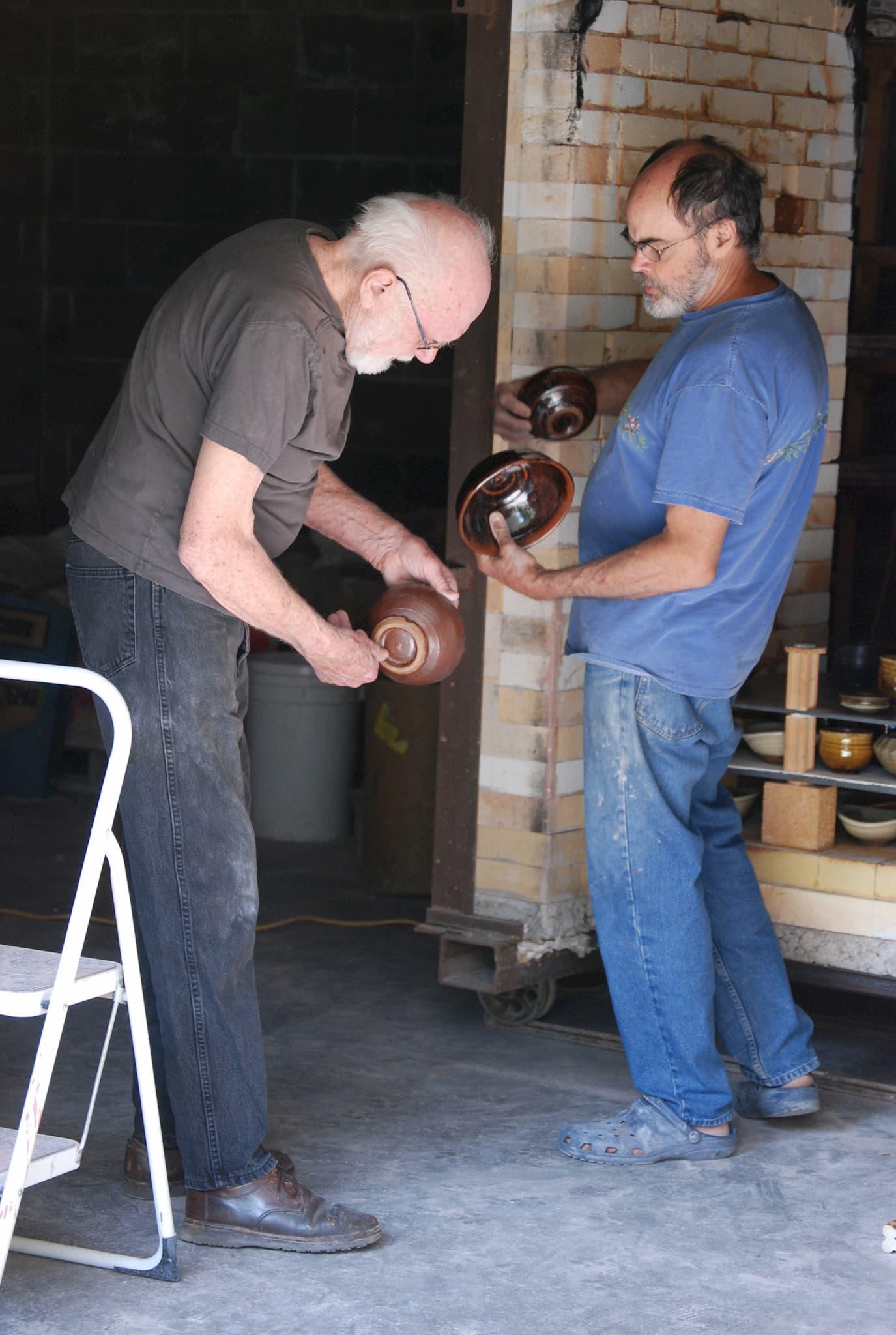 Warren MacKenzie & Guillermo Cuellar inspect the results of a firing, 2015. Courtesy of Guillermo Cuellar